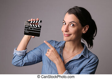 Woman holding a movie clapper - Smiling attractive woman in...