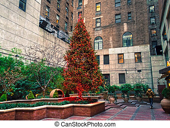 Christmas Tree in Courtyard - A christmas tree with red...