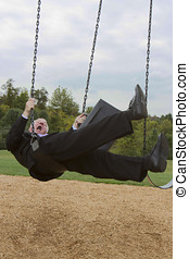 Businessman twisting uncontrollably on a swing set