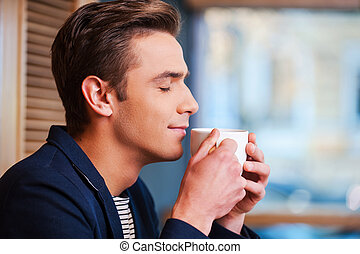 Enjoying the best coffee in town Side view of handsome young...