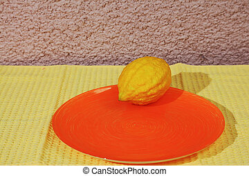 Ritual fruit - citron on orange plate and yellow napkin...