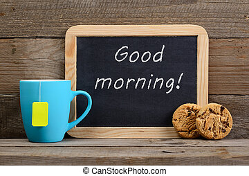 Cup of tea, cookies and blackboard with Good morning! phrase