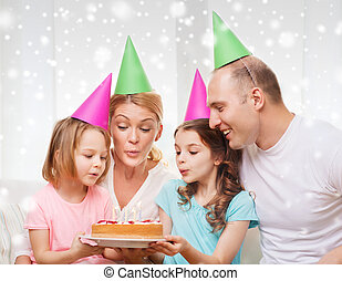 happy family with two kids in party hats at home