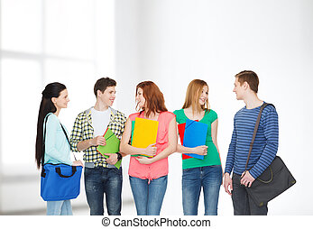 group of smiling students standing - education and people...