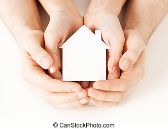 man and woman hands with white paper house - real estate and...