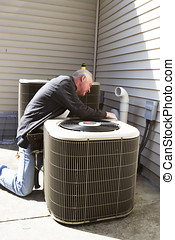 Repairman servicing or fixing an outdoor airconditioner unit