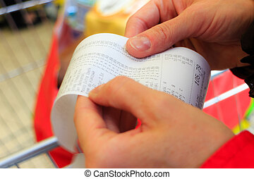 Supermarket. paper check receipt bill in hand. - Supermarket...