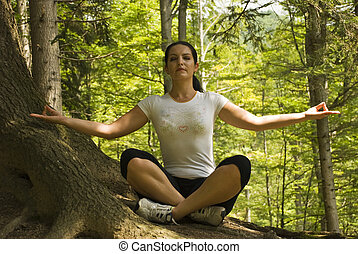 Woman doing yoga in forest at mountain,in nature in a sunny...