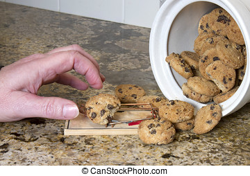 Hand reaching for chocolate chip cookie sitting on a...