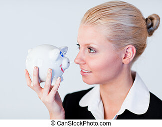 Businesswoman holding a piggy bank