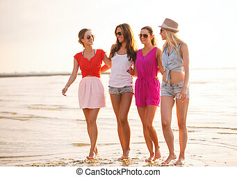 group of smiling women in sunglasses on beach - summer...