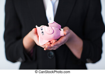 Business woman holding a broken piggy bank - Young Business...