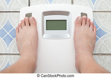 Man steps on digital weight machine
