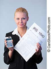 Filling in tax returns - Business woman looking at filling...