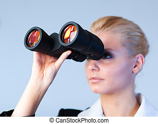 Serious business woman looking into Binoculars