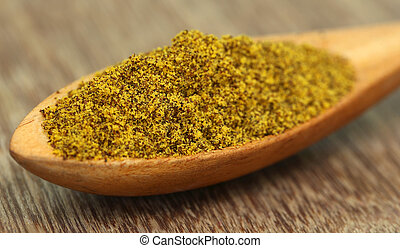 Grated Mustard in a wooden spoon