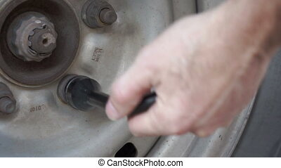 Car Tire Loosening Nut - Close up shot of an anonymous...