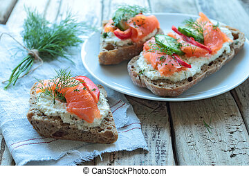 Plate with sandwiches with salmon on a wooden table boards