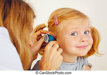 Pediatrician doctor examining little girl ears.