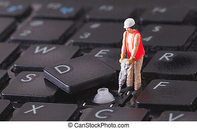Miniature worker with drill working on keyboard