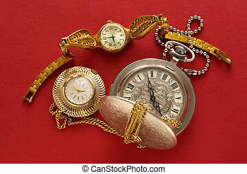 Two pocket watches and handwatch on red