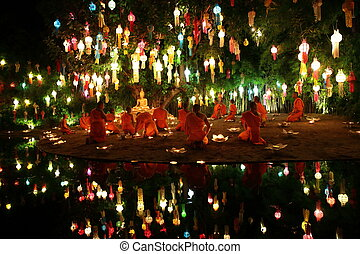Thai monks meditate around buddha statue among many lanterns...