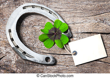 Horseshoe and four leaf clover with empty tag on old wooden