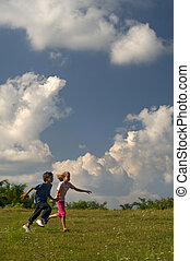 Children playing and running on meadow against blue sky