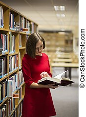 Woman in library near shelves with book