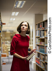Woman in library between shelves with book