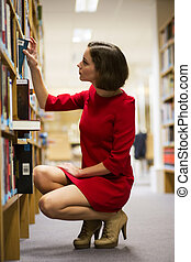 Woman in library found book for reading - Young woman in...