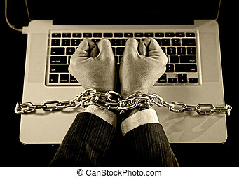 Hands of businessman addicted to work bond with chain to...