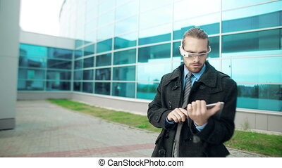 Multi-Gadget Work - Man using electronic eyewear and digital...