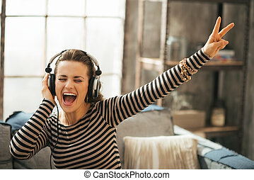 Cheerful young woman listening music in headphones in loft...