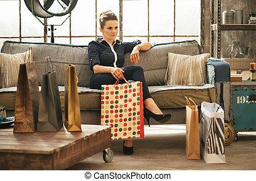 relaxado, jovem, mulher, com, shopping, sacolas, sentando,...