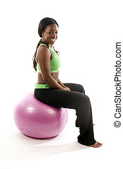 young and pretty hispanic latina black woman wearing exercise tights and working out with fitness core ball