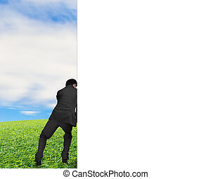 man pushing away white empty wall with nature sky clouds...