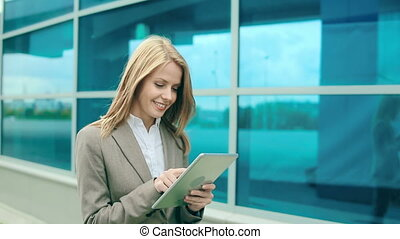 Business Technology - Pretty young businesswoman using...