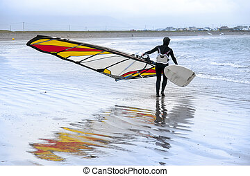 lone windsurfer getting ready to surf on the beach in the...