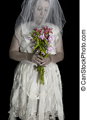 Older woman dressed in tattered wedding dress and veil...