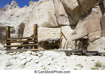 Entrance buildings to abandoned mine shaft on side of canyon wall