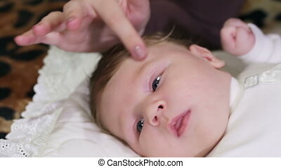 Touching baby - Young mother caresses and soothes baby