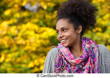 Young african american woman smiling outdoors in autumn -...