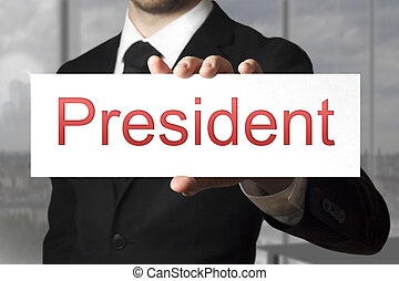 businessman holding sign president - businessman in black...