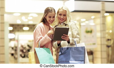 happy young women with tablet pc and shopping bags - sale,...