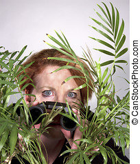 Woman looking through plant with binoculars