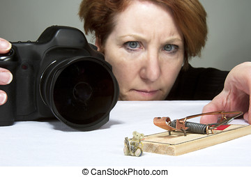 Female photographer setting up a scene with a mouse and...