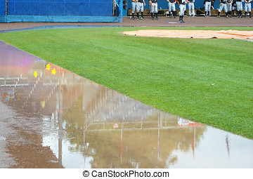 Rubber duckies in a puddle along the first base line in a...