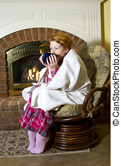Mature woman dressed in flannel pajamas sitting in a chair...