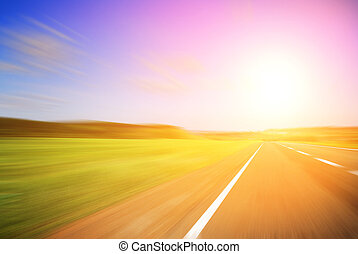Blurred road and blurred sky with a shining sun
